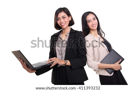 Two beautiful Asian female professionals posing with their laptop and notebook, isolated on white background - stock photo