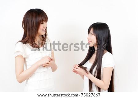 two beautiful asian women talking - stock photo