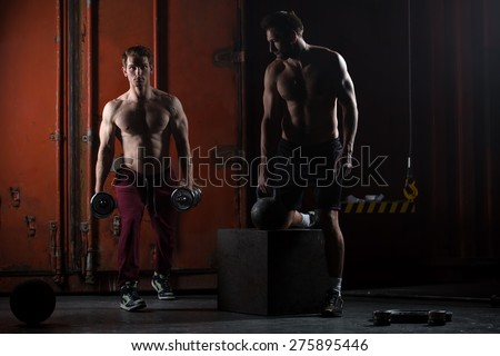 Two beautiful athlete train. One does kettlebell swings, squats with dumbbells other. The picture in the studio in a dark tone. - stock photo