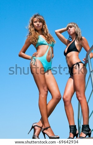 Two beautiful bikini model against blue sky - stock photo