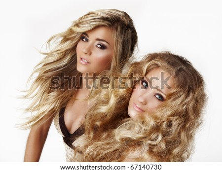 two beautiful blond woman sisters with styled blond hair blowing ion the wind on white background - not isolated.
