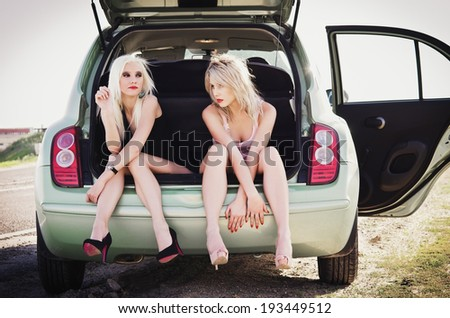 Two beautiful blonde girls sitting in a trunk of broken car and waiting for help - stock photo