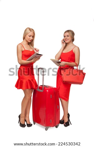 two beautiful blonde girls wearing red dresses with big suitcase and bag and tablet isolated on white  - stock photo