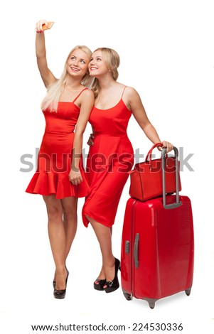 two beautiful blonde girls wearing red dresses with big suitcase and bag making selfi using cell phone isolated on white  - stock photo