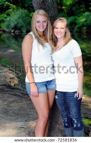 Two beautiful blonde sisters standing together along a creekbank - stock photo
