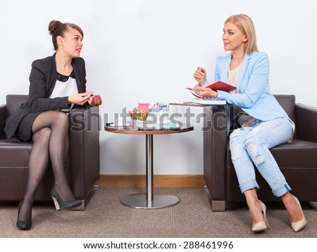 two beautiful businesswoman are talking in the office - stock photo