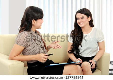 two beautiful businesswoman office worker discussing in the office - stock photo