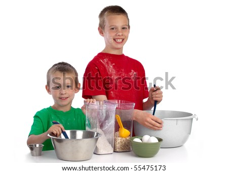 Two beautiful caucasian brothers making a cake in the kitchen, smiling happily, isolated on white background