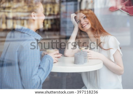 Two beautiful cheerful young women smiling and drinking coffee in cafe together - stock photo