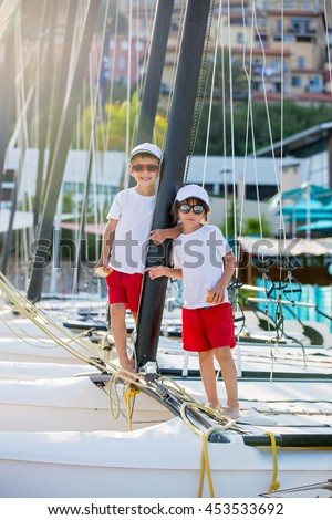 Two beautiful children, boy brothers, standing on a boat, smiling, summertime on sunset - stock photo