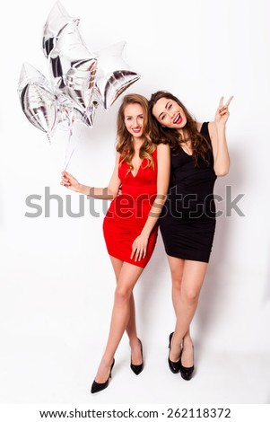 Two beautiful elegant brunette  women with red lips in evening black and red dress on the party . One keeping silver stars balloons in her hand and smiling against white background.   - stock photo