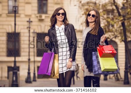 two beautiful fashion models posing outside with shopping bags; two young women laughing, having fun, wearing sunglasses - stock photo