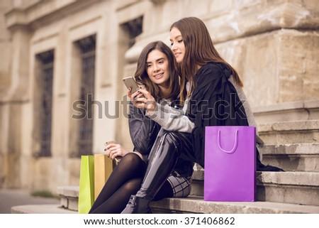 two beautiful fashion models with shopping bags; two young women laughing, having fun, checking the phone, or taking a selfie; shopping break - stock photo