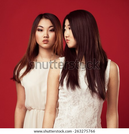 Two beautiful fashionable woman in white gowns against red background