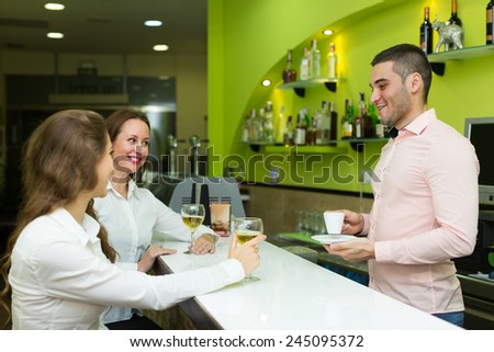 Two beautiful female friends chatting and drinking wine in the bar - stock photo
