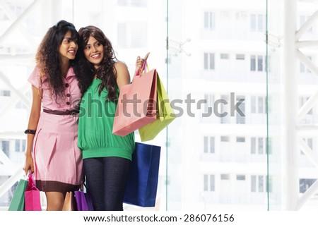 Two beautiful friends enjoying while shopping - stock photo