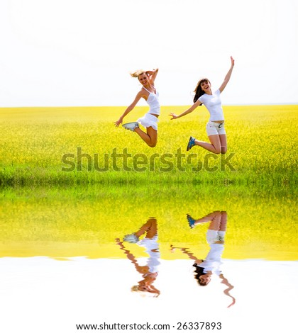 Two beautiful girl in white clothes jumps the yellow flowers - stock photo
