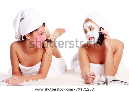 Two beautiful girl relaxing in spa with nutrient facial masks - stock photo