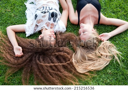 Two beautiful girl with long hair lying on green grass in the afternoon - stock photo