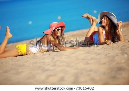 Two beautiful girls at beach - stock photo