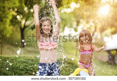 Two beautiful girls having fun outside in the garden - stock photo