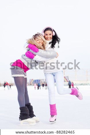 two beautiful girls ice skating outdoor on a warm winter day