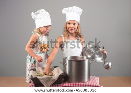 Two beautiful girls in clothes cooks prepare a delicious meal. The child in the kitchen putting the vegetables in a large pot. - stock photo