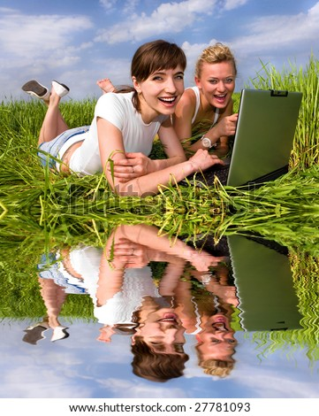Two beautiful girls in white clothes are laughing near laptop computer outdoors. Lay on the green grass.