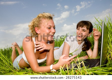 Two beautiful girls in white clothes are laughing near laptop computer outdoors. Lay on the green grass. - stock photo