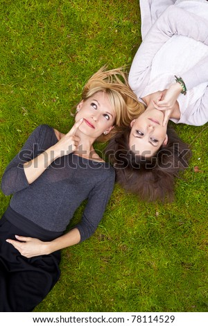 Two beautiful girls lying in the grass and thinking. - stock photo