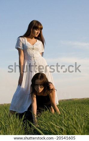 Two beautiful girls on the green grass, one is over the other - stock photo