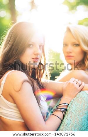 Two beautiful girls outdoors backlight portrait. - stock photo