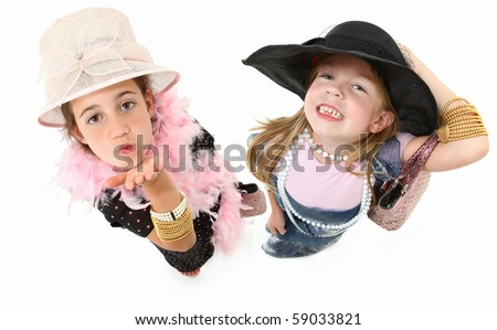 Two beautiful girls playing dress up with hats, baggy dresses and jewelry over white. - stock photo