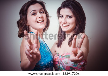 two beautiful girls positive on gray background