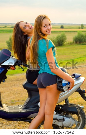 Two beautiful girls resting after riding scooter on sunny summer day. - stock photo