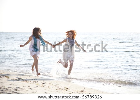Two beautiful girls running on the beach.