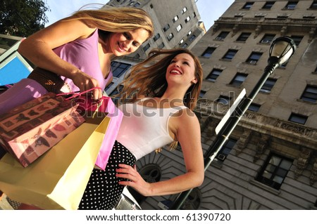 two beautiful girls shopping together in the city street - stock photo
