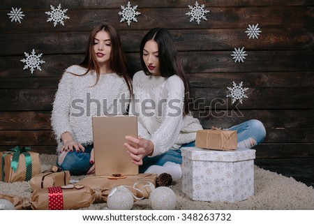 Two beautiful girls sitting on the floor with a tablet, between gifts for Christmas