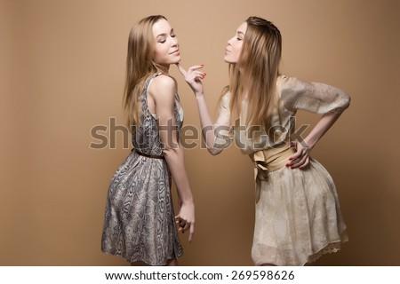 two beautiful girls twins in the studio, sisters, flirt, - stock photo