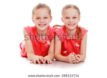 Two beautiful girls twins school age, lie on the floor-isolated on white background - stock photo
