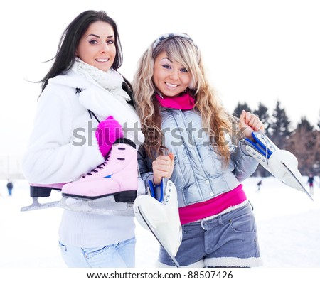 two beautiful girls wearing warm winter clothes going  ice skating - stock photo