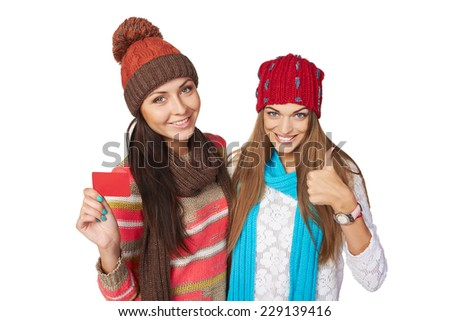 Two beautiful girls wearing winter hats, mufflers showing blank red card and gesturing thumb up - stock photo