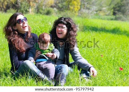 two beautiful girls with a baby in the background of the spring forest - stock photo