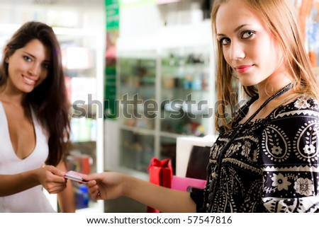 Two beautiful girls with card - stock photo