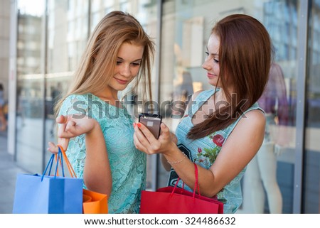 Two beautiful girls with colorful shopping bags and mobile phone - stock photo