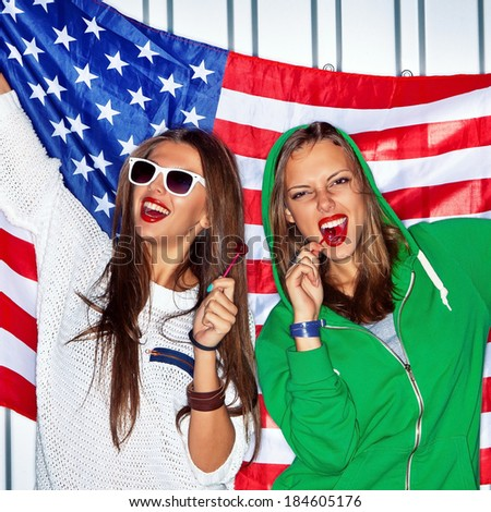 Two beautiful girls with red lollipops holding a flag of the USA - stock photo
