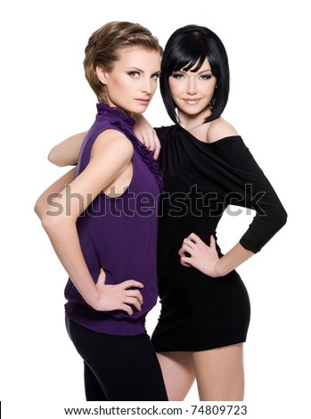 Two beautiful  glamour women standing together over white background - stock photo