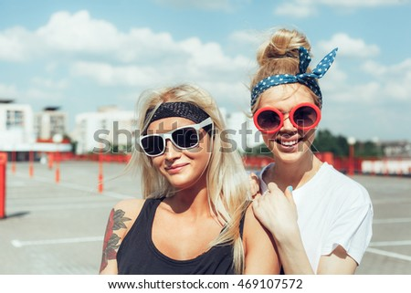 Two beautiful happy girls in sunglasses looking into the distance on the urban background. Young active people. Outdoors