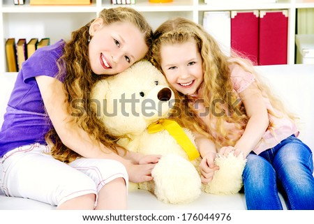 Two beautiful happy sisters playing together at home. - stock photo