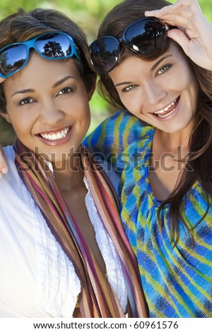 Two beautiful interracial young women in their twenties wearing sunglasses, laughing and having fun on vacation, shot in golden sunshine in a tropical resort location. - stock photo